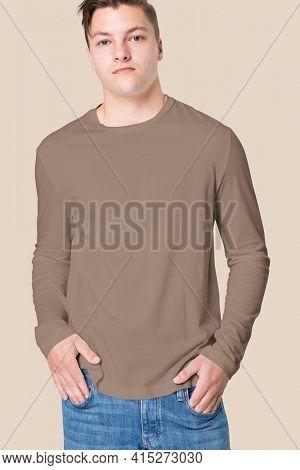 Man in brown long sleeve tee men's fashion studio portrait