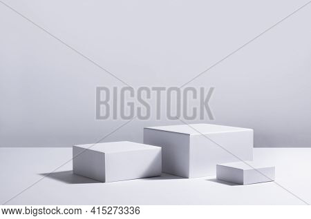 White Square Podiums In Sunlight With Shadow In White Space. Showcase For Cosmetic Products, Goods,