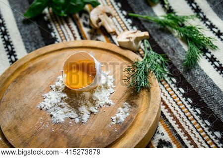Broken Egg In Flour On Round Cutting Board, On Dark Wooden Table With Napkin Top View