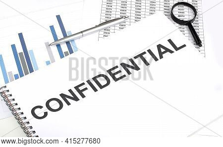 In The Notebook, The Text Confidential , Next To Magnifier And Pen, Background Is Graphics.