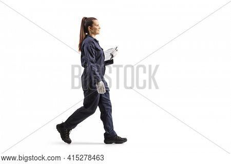 Full length portrait of a female worker in a uniform walking and holding a clipboard isolated on white background