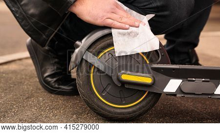 A Man Wipes His Electric Scooter With A White Damp Cloth. Cleaning Dirty Scooter