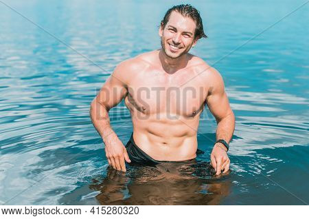 Muscular Young Athletic Sexy Man On The Beach With A Fit Torso. Strong And Handsome. Portrait Of You