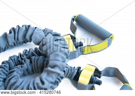 Grey And Yellow Handles Of Latex Resistance Band Scrunched In Nylon Safety Sleeve Isolated On A Whit