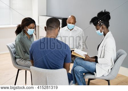 Group Of People Study Religious Book With Preacher In Face Mask