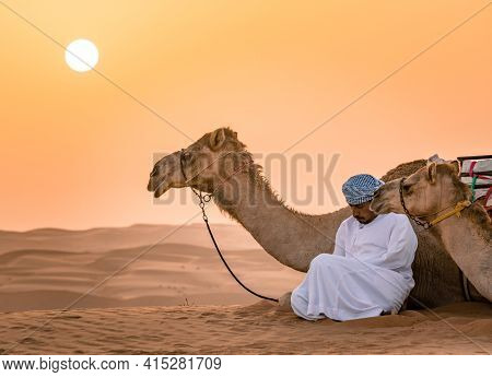 Wahiba Sands,oman - 04.07.2018: A Man In White Robe And His Camel Sit On The Desert Sand. Early Morn