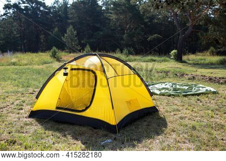Installed Tourist Tent And A Camping Lantern In Nature In The Forest. Domestic Tourism, Active Summe