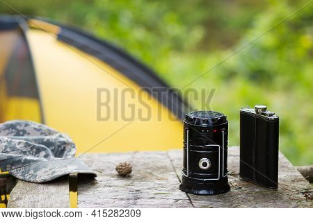 Camping Portable Lantern On A Road Pole With A Tent In The Background. The Concept Of Hiking In Natu
