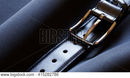 A Leather Belt With A Gold-tone Buckle Rests Against A Dark Textile Background. Macro. Close-up