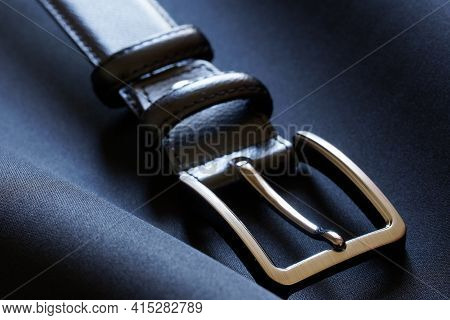 A Polished Metal Buckle Of A Leather Belt Rests On A Dark Blue Textile Background. Macro. Close-up