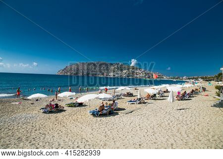 Alanya, Turkey -October 20, 2020: People relaxing on the sandy beach in Alanya,  Turkey.