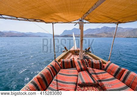 View From The Traditional Arabian Dhow Boat Sailing On The Sea. Red Pillows And Carpets, Yellow Fabr