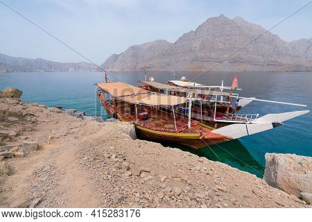 Two Traditional Arabian Dhow Boats Parked By An Island In Turquoise Fjords Of Musandam, Oman. Hot, H