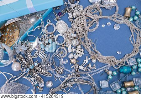 A Set Of Silver Jewelry. Space For The Text. Blue And Silver Jewelry On A Blue Background. Top View