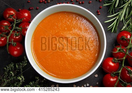 Top View Of A Bowl Of Tomato Cream Soup. The Ingredients Are Arranged Around The Bowl: Cherry Tomato
