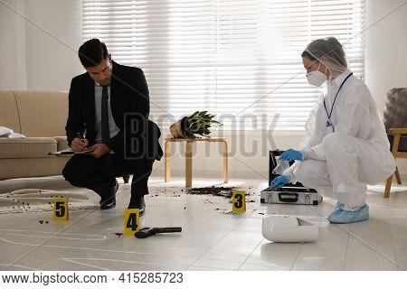 Investigators Examining Crime Scene In Living Room