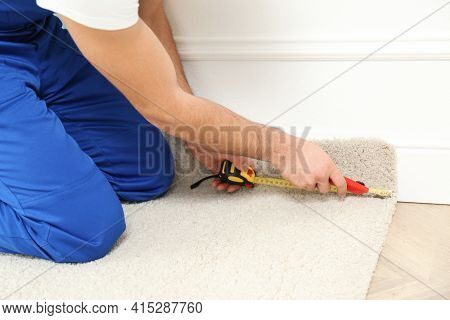 Worker With Cutter Knife And Measuring Tape Installing New Carpet Indoors, Closeup