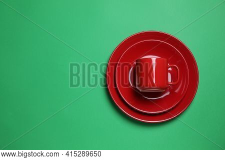 Set Of Red Ceramic Dishware On Green Background, Top View. Space For Text