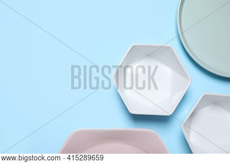 Set Of Ceramic Dishware On Light Blue Background, Flat Lay. Space For Text