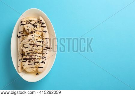Delicious Banana Split Ice Cream With Toppings On Light Blue Background, Top View. Space For Text