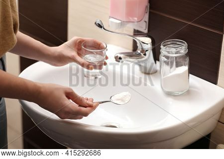 Woman Using Baking Soda To Unclog Sink Drain In Bathroom, Closeup