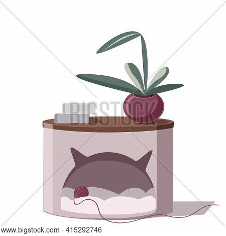 A Cozy House For A Cat In The Form Of A Bedside Table. A Potted Flower, Book, And A Ball Of Woolen T