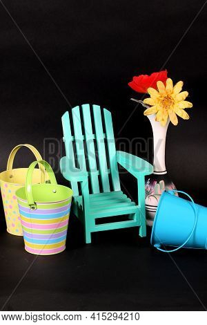 Sand Pails, Toy Adirondack Chair And Silk Flowers In Vase Shot In Studio Showing Spring And Summer A