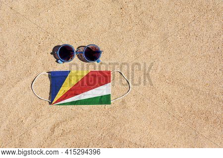 A Medical Mask In The Color Of The Seychelles Flag Lies On The Sandy Beach Next To The Glasses. The