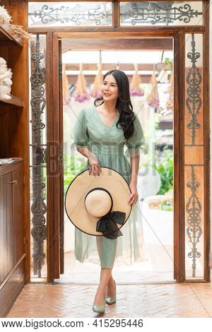 Happy Young Beautiful Woman Gracefully Walking Into Her House While Holding Her Straw Hat And Smilin