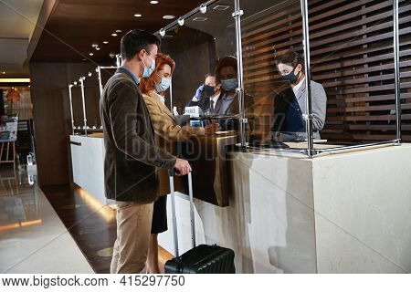 Guests Filling In The Registration Form At The Reception Desk