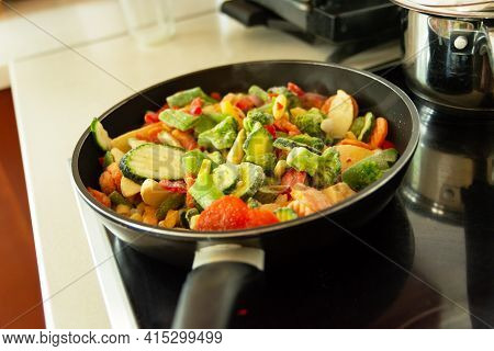 Frozen Fresh Vegetables In A Pan On An Induction Hob