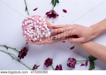 Close-up Of Beautiful Sophisticated Female Hands With Pink Flowers And Donut On A White Background.