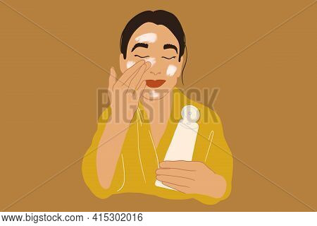 Pretty Woman Apply Cream Or Scrub On Face In Yellow Bathrobe While Holding A Tube. Clean And Beauty