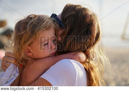 Little Girl Daughter Hugs A Woman To Her Mother On The Beach. Happy Modern Mother And Girl Child On