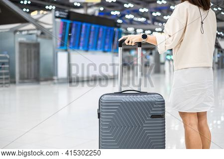 Young Woman Hand Holding Luggage Handle Before Checking Flight Time In Airport, Transport, Insurance