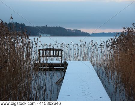 Bathing Pier With Bench And Reed In Winter Morning In Winter Snow At Frozen Lake