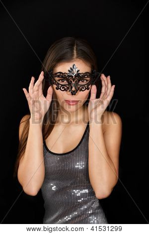 Woman wearing mask. Mysterious young woman wearing carnival mask isolated on black background. Multi cultural Asian Caucasian girl.,