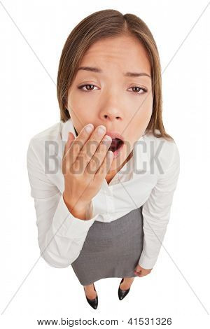 Exhausted or bored woman in yawn. Humorous high angle view of an exhausted or bored young woman yawning with her hand to her mouth and apathetic eyes, isolated on white background.
