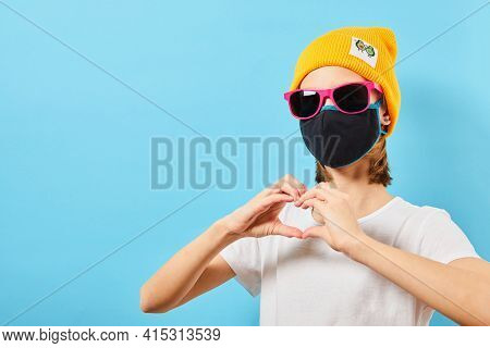 Hipster Teen In Trendy Glasses Wearing Knitted Hat Showing Heart Gesture. Young Girl On Blue Backgro