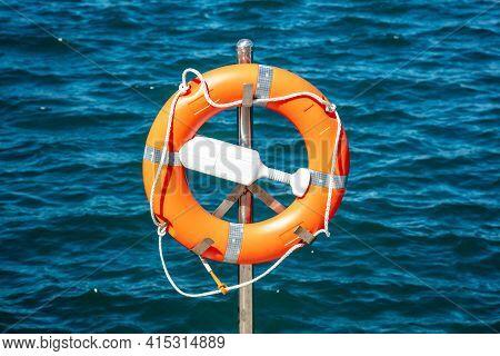 Lifebuoy Orange On Vertical Iron Against Blue Sea Background.