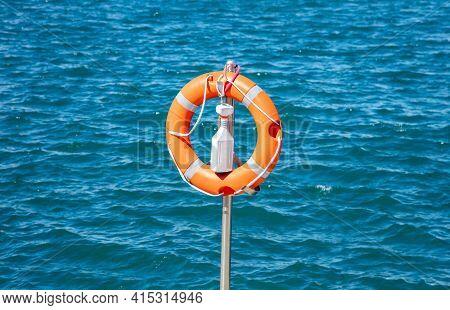 Buoy Concept. Lifebuoy, Orange Lifebelt Put On Silver Vertical Iron Ready For Using. Circle Lifesave