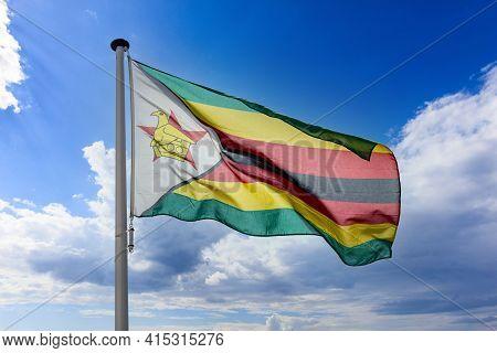 Zimbabwe Flag, Republic Of Zimbabwe National Symbol On A Flagpole Waving Against Blue Cloudy Sky