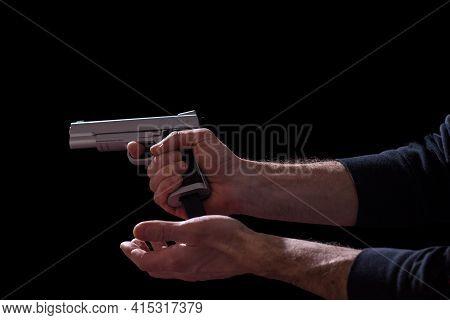 Male Hands Reloading Gun Magazine, Isolated On Blackbackground.
