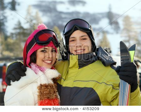 Young happy couple in winter clothes and gogles in skiing resort poster