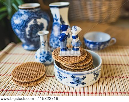 Delfts Blue Decorative Crockery Set On The Table With Traditional Dutch Cookies Stroopwafels,