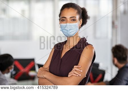Portrait of young businesswoman wearing protective face mask standing in modern office and looking at camera for protection against coronavirus. Portrait of black businesswoman with crossed arms.