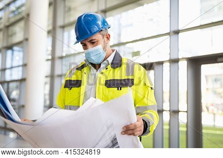 Architect studying draft while visiting construction site and wearing surgical face mask to protect himself from covid virus. Architect builder studying layout plan of construction site.