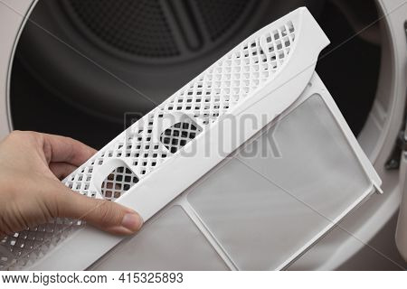 A Womans Hand Takes Out The Filter Of The Drying Machine. Down Filter For Clothes Dryers. Removing F