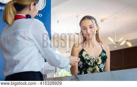 Young Travellers Standing At Reception Desk With Female Receptionist Standing At Hotel Counter, Happ