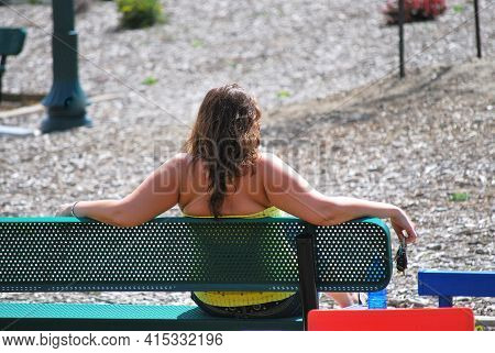 Female Beauty Relaxing On A Park Bench Alone Outside.